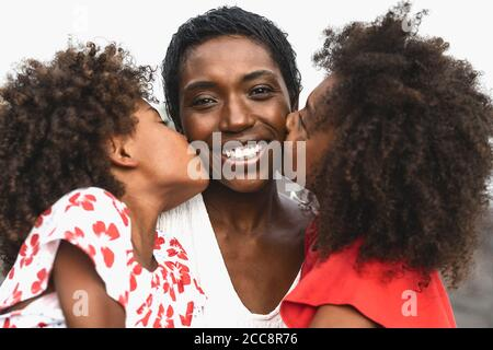 Happy African family having fun on the beach during summer holidays - Portrait of Afro people enjoying vacation days