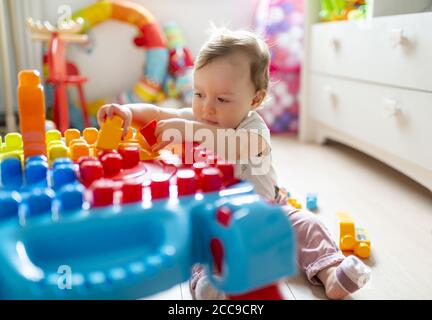 Baby girl (16 months) sitting on the floor and playing in her bedroom with colourful Mega Bloks® plastic blocks near her white wooden chest of drawers