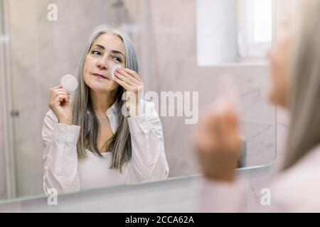 Skin care and hygiene concept. Charming senior gray haired lady using a cotton pad with micellar water for removing make up from face, standing in - Stock Photo