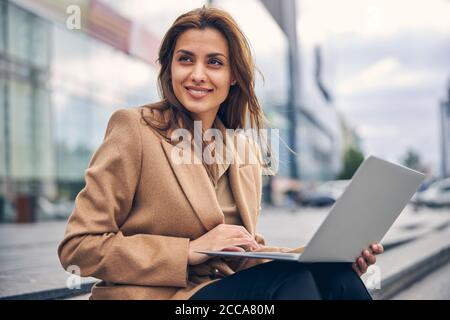 Pleased business lady in a trendy jacket sitting outdoors