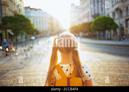 Life during covid-19 pandemic. Seen from behind girl in white polka dot blouse with pink mask and yellow backpack going from school outdoors. - Stock Photo