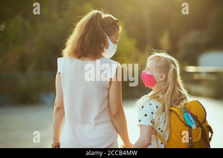 Life during covid-19 pandemic. Seen from behind young mother and child with masks, yellow backpack and antiseptic coming back from school outside. - Stock Photo