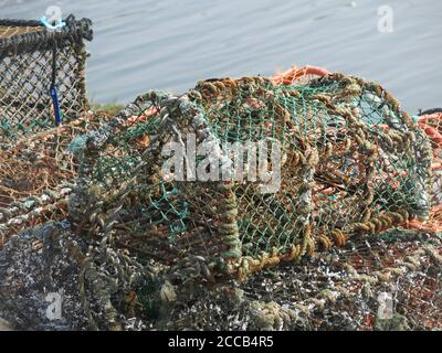 Close up of lobster cages on the quayside at St Andrews; made from a wooden frame with mesh. - Stock Photo