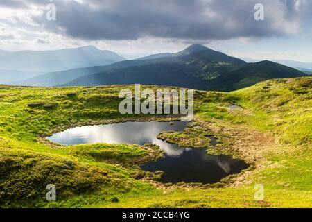 Mountain lake on sunrise time. Picturesque summer landscape with green mountain hills and sun rays in morning sky. Carpathian mountains