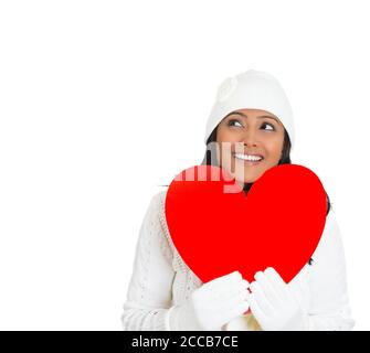 Closeup portrait of young beautiful pretty woman wearing winter gear attire sweater holding red valentine heart looking up, isolated on white backgrou - Stock Photo