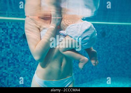 Mom and baby swim in the pool. - Stock Photo