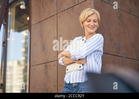 Smiling lady with a computer looking down