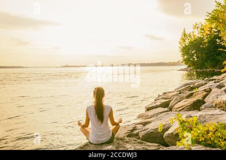 Yoga class outside in nature park by lake river shore. Woman sitting in lotus pose meditating by the water in morning sun flare sunrise. Meditation