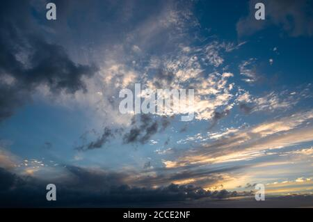 A mixture of clouds in the sky at sunset. Darker dissipating stratocumulus is visible beneath altocumulus and cirrus being lit by the setting sun. - Stock Photo