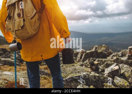 man in yellow coat standing on the top of mountain looking at the distance. close up cropped photo