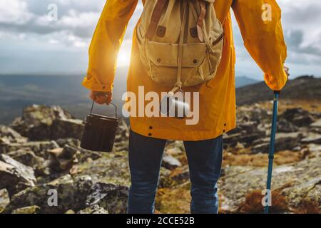 Cropped image of a tourist walking along hiking trail with bucket. close up back view cropped photo