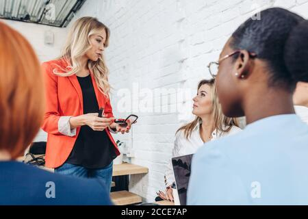 Young female expert in red jacket makes a presentation at a meeting in the office. Blonde woman sharing information with company of young friends.