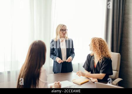 Group of business women meeting at the office. Blonde woman dressed in formal suit sharing her ideas with two colleagues, sitting at the desk.