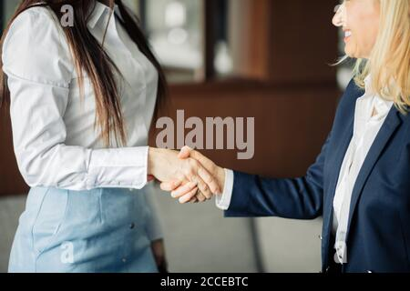 Have a good day. Two female co-workers greeting, parting or congratulate each other while meet in the office. Greeting, welcome, farewell concept