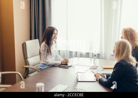 Three focused caucasian young business women with different hairstyle working together, brainstorming in office. Stock Photo