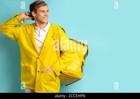 attractive young caucasian guy 20-25 years old work as courier in delivery service, pleasant man in yelow uniform stand isolated over blue background - Stock Photo