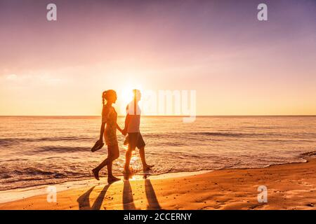 Couple walking on beach at sunset silhouettes - Romantic summer travel holidays in Caribbean destination