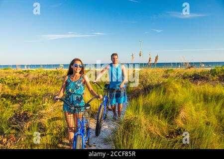 Summer people lifestyle happy couple biking on beach relaxing outdoors activity at sunset. Young woman and man riding recreational bikes bicycles on Stock Photo