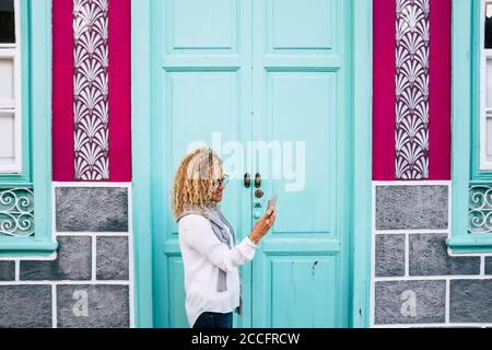 Attractive woman with curly blonde hair using smart phone standng in the street - light blue door in background Stock Photo