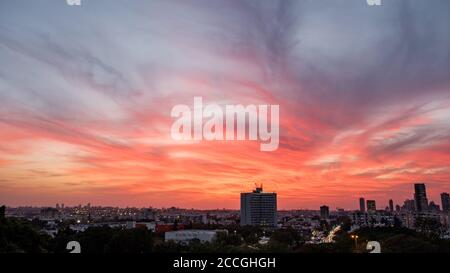 A dramatic sunset skies with fire colored light clouds over Tel Aviv city, Israel. - Stock Photo