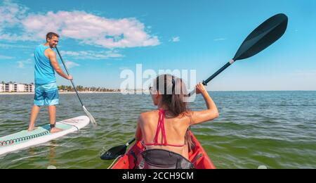Couple kayaking and paddle boarding fitness man in ocean Paddleboard beach people on stand-up paddle boards surfing in Tourists kayakers woman and man - Stock Photo