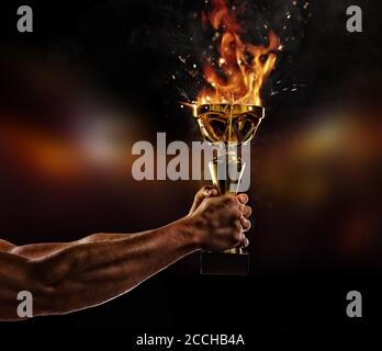 Muscular man arm holding burning trophy cup on black background. Detail of fighter hand. Concept of success, hard work and conquest of the target. Hig