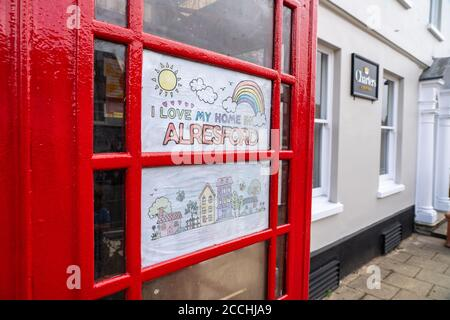 'I love my home in Alresford'. Child's drawing in telephone box with rainbow. Spreading hope during Covid 19 crisis.