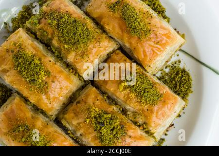 Traditional Turkish Pastry Dessert,Pistachio Baklava in plate at white surface with copy space