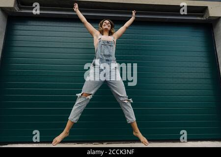 Carefree young woman jumping in front of garage door