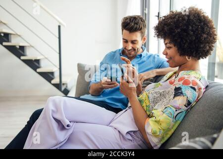 Couple using smart phones while sitting on sofa in modern penthouse