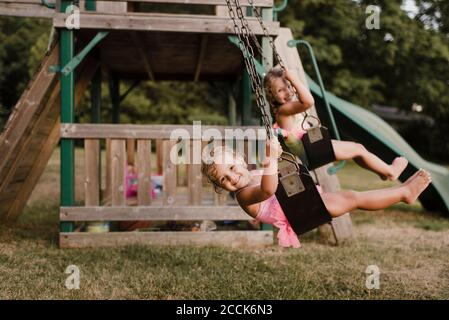 Happy girls with wet hair on a swing - Stock Photo