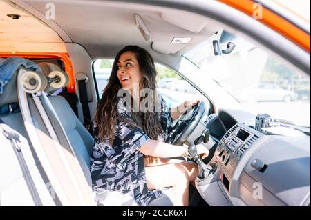 Young woman driving camoer with skateboard on passaenger seat