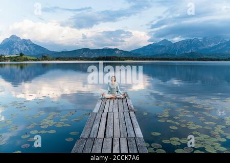 Woman meditating while sitting on jetty over lake against cloudy sky - Stock Photo