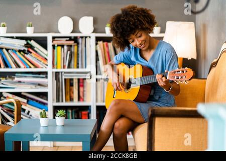 Happy woman playing guitar while sitting on sofa in coffee shop - Stock Photo