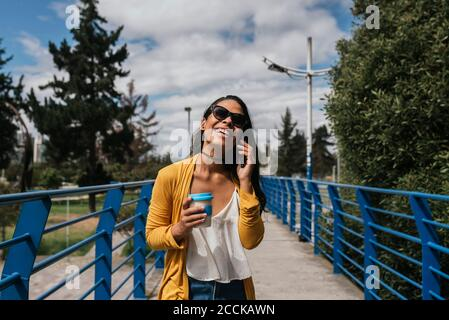 Cheerful woman wearing sunglasses talking over smart phone while standing on footbridge in park - Stock Photo