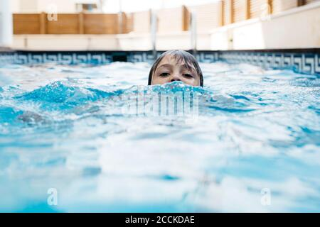 Boy swimming in pool during summer - Stock Photo