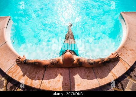 Man relaxing in swimming pool during sunny day - Stock Photo