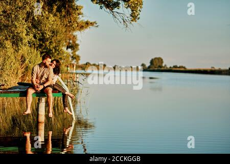 Couple reflected in water sitting on jetty at a lake