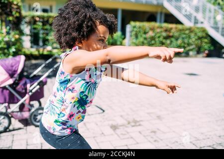 Playful baby girl pointing while standing on footpath during sunny day