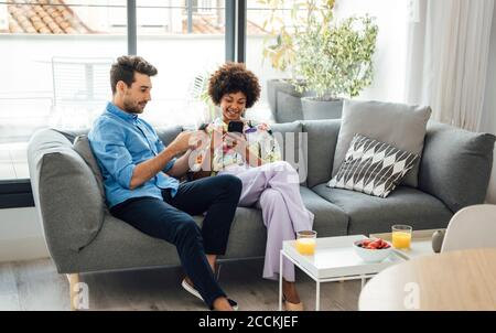 Multi-ethnic couple using smart phones while sitting on sofa in penthouse