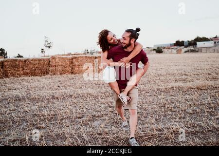 Smiling man giving woman piggyback ride against straw in field - Stock Photo