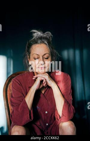 Close-up of senior woman with eyes closed sitting on chair against curtain at home
