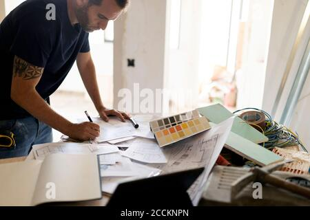 Man working on construction plan and colour swatch