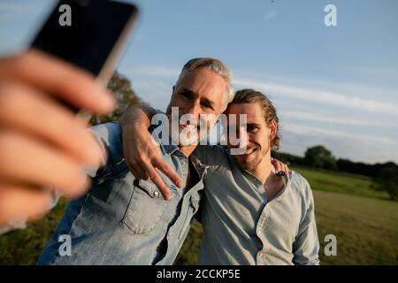 Happy father with adult son taking a selfie on a meadow in the countryside