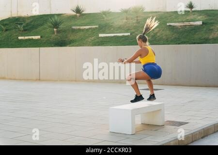 Young athletic woman during workout jumping on a bench - Stock Photo