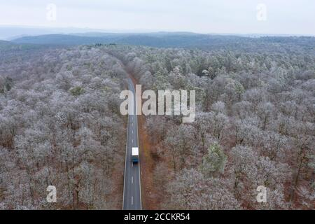 Germany, Bavaria, Drone view of truck driving along asphalt road cutting through Steigerwald forest in winter - Stock Photo