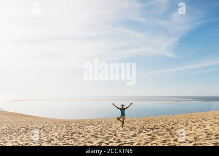 Woman looking at Atlantic ocean while exercising on beach during sunny day, Dune of Pilat, Nouvelle-Aquitaine, France - Stock Photo