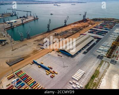 Thessaloniki, Greece Aerial drone landscape view of city port area. Day top panorama of large motorized cranes on sea port, with cargo pier containers