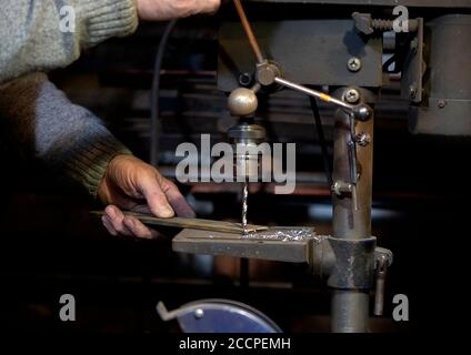 Blacksmith uses drill press in garage. A close up view of a metalworker operating a bench drill inside his workshop. Heavy duty machine is used for dr - Stock Photo