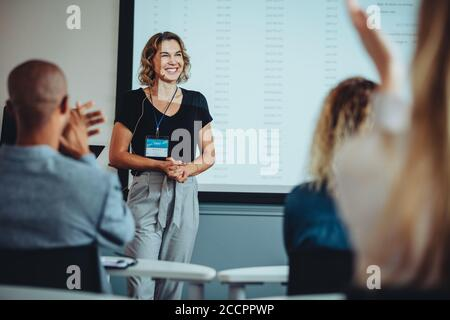 Team of professionals clapping hands in a meeting for a female presenter. Business people appreciating the presentation by a female colleague. Stock Photo